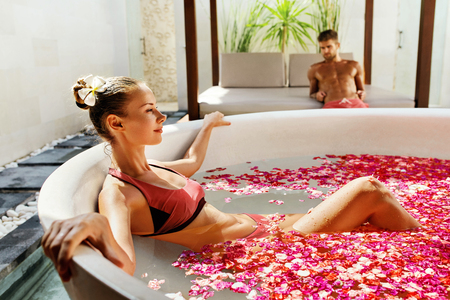 aroma therapy: Woman In Bath At Day Spa Salon. Beautiful Smiling Girl In Bikini Bathing, Bathe With Flower Petals In Summer. Sexy Female Relaxing Outdoors. Aroma Therapy Beauty Treatment, Body Care. Relax Concept