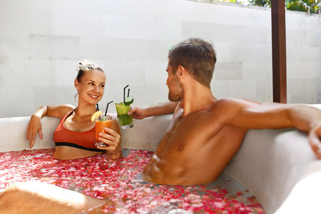 personas banandose: Spa Relax. Pares en el amor que se relaja, se baña en flor al aire libre baño en el Día de salón de lujo. Hombre guapo y saludable Mujer sonriente que bebe el zumo de cóctel beber en verano de vacaciones de luna de miel. relaciones