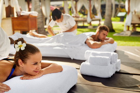 relax massage: Spa Couple Massage. Beautiful Happy Smiling Woman And Healthy Man Enjoying Relaxing Body Massage Treatment Outdoors At Beauty Salon. People At Romantic Day Spa Resort. Health Care And Relax Concept