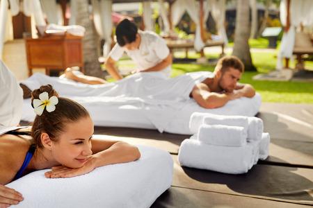 cuerpo hombre: Spa masaje en pareja. Hermosa feliz sonriente Mujer y Hombre sano goza de relajante masaje del cuerpo de tratamiento al aire libre del salón de belleza. La gente en el día romántica Spa Resort. Cuidado de la Salud y Relax Concept