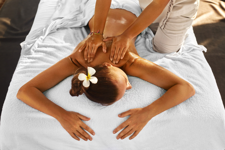 Spa Massage For Woman. Therapist Massaging Female Body With Aromatherapy Oil. Beautiful Healthy Happy Girl Relaxing Back Massage At Beauty Salon Outdoors. Skin Care Treatment, Health And Relaxation