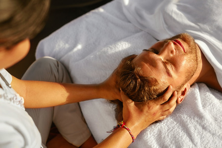 Massage Spa. Gros plan de belle santé Heureux homme appréciant relaxant Head Massage à l'extérieur Salon Day. Masseur Hands Masser Handsome Head Homme. Relax Soins de beauté pour les hommes, les soins de santé Concept Banque d'images