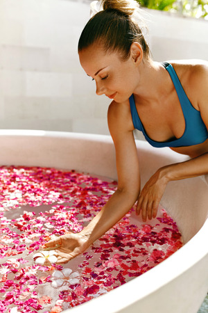 aroma therapy: Day Spa Body Care. Beautiful Sexy Happy Woman With Healthy Skin In Bikini Relaxing Near Round Outdoor Bath With Tropical Flower Petals, Enjoying Summer. Bathing Beauty Treatment, Aroma Therapy, Health Stock Photo