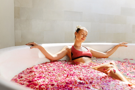 bath: Woman In Bath At Day Spa Salon. Beautiful Smiling Girl In Bikini Bathing, Bathe With Flower Petals In Summer. Sexy Female Relaxing Outdoors. Aroma Therapy Beauty Treatment, Body Care. Relax Concept