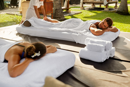 Couple Treatment At Spa. People In Love Enjoying Body Massage Outdoors At Day Spa Resort. Beautiful Woman, Handsome Happy Healthy Man Relaxing On Romantic Honeymoon Vacation In Summer. Relax Concept