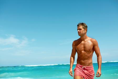 Sexy Mann am Strand im Sommer. Stattlicher Mann mit Fit Körper, gesunde Haut Sun Tan Tanning in der Nähe von Meer bei Luxury Relax Spa Resort. Schöne glückliche Guy entspannen, genießen Urlaub einen unvergesslichen Urlaub. Sommer
