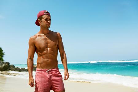 Sexy Mens Op Strand In De Zomer. Knap Mannetje Met Fit Body, gezonde huid Zon Tan Tanning nabij Sea Op Luxury Relax Spa Resort. Mooi Gelukkig Guy Ontspannen, genieten van vakantie vakantie. zomertijd
