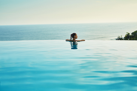 Luxury Resort. Woman Relaxing In Infinity Swimming Pool Water. Beautiful Happy Healthy Female Model Enjoying Summer Travel Vacation, Looking At Sea View. Summertime Recreation, Relax And Spa Concept. Archivio Fotografico