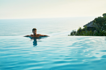 hotel indonesia: Luxury Resort. Man Relaxing In Infinity Swimming Pool Water. Beautiful Happy Healthy Male Model Enjoying Summer Travel Vacation At Tropical Spa Hotel In Indonesia, Sea View. Summertime Relax Concept