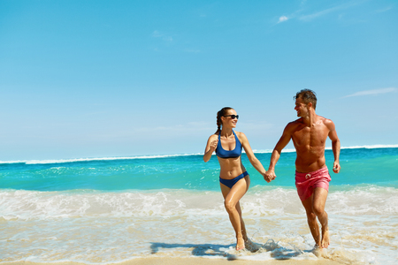 Couple Fun On Beach. Romantic People In Love Running On Sand At Luxury Sea Resort. Handsome Happy Man, Beautiful Smiling Woman Laughing Together On Summer Travel Vacation. Relationships, Summertime