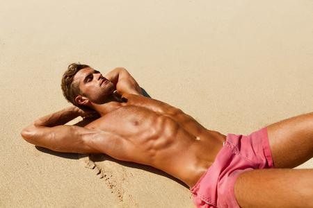 Man Körper am Strand im Sommer. Gutaussehend Sexy Fit Male mit gesunder Haut Sun Tan Tanning in Luxus-Relax Spa Resort. Schöne Fitness Model Entspannen, Sonnenbaden liegen auf Sand. Sommer Reisen Urlaub