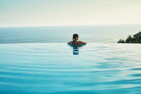 Luxury Resort. Woman Relaxing In Infinity Swimming Pool Water. Beautiful Happy Healthy Female Model Enjoying Summer Travel Vacation, Looking At Sea View. Summertime Recreation, Relax And Spa Concept. 스톡 콘텐츠