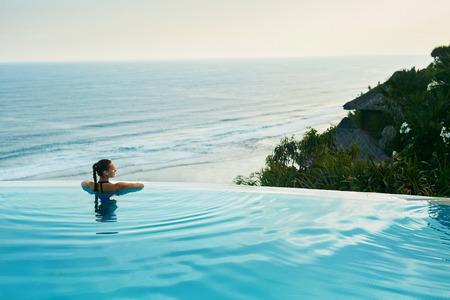 럭셔리 리조트. 인피니티 수영장 물에 편안한 여자. 아름다운 해피 건강한 여성 모델은 바다보기,보고 여름 여행 휴가를 즐기고있다. 여름 레크리에이