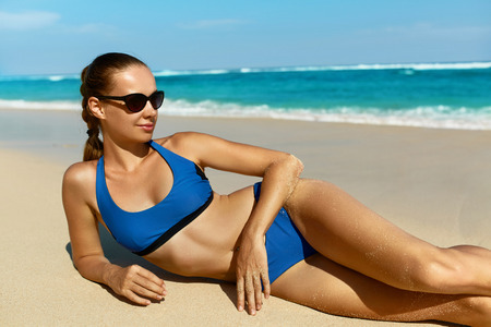sun tanning: Woman On Beach In Summer. Sexy Happy Female Model Sun Tanning On Sand. Beautiful Girl With Fit Body, Healthy Tan Skin In Sport Bikini, Sunglasses Relaxing At Sea Resort On Vacations. Summertime Relax Stock Photo