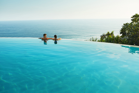 Romantic Vacation For Couple In Love. Happy People Relaxing In Infinity Edge Swimming Pool Water, Enjoying Beautiful Sea View. Man, Woman Together On Summer Travel To Luxury Resort. Summertime Relax Stock Photo