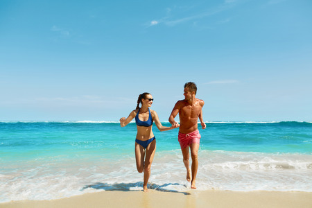 bikini couple: Couple Fun On Beach. Romantic People In Love Running On Sand At Luxury Sea Resort. Handsome Happy Man, Beautiful Smiling Woman Laughing Together On Summer Travel Vacation. Relationships, Summertime