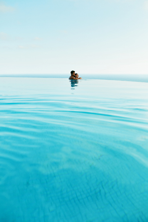 honeymoon: Couple In Love At Luxury Resort On Romantic Summer Vacation. People Relaxing Together In Edge Swimming Pool Water, Enjoying Beautiful Sea View. Happy Lovers On Honeymoon Travel. Relationship, Romance