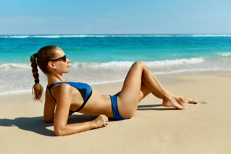 seaside: Woman On Beach In Summer. Sexy Happy Female Model Sun Tanning On Sand. Beautiful Girl With Fit Body, Healthy Tan Skin In Sport Bikini, Sunglasses Relaxing At Sea Resort On Vacations. Summertime Relax Stock Photo