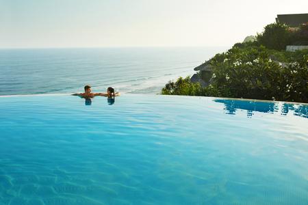 Romantische Urlaub für Paare in der Liebe. Happy People Entspannung im Infinity-Pool Wasser, genießen Sie einen wunderschönen Blick auf das Meer. Mann, eine Frau zusammen auf Sommer-Reise zum Luxus-Resort. Sommer Relax Standard-Bild
