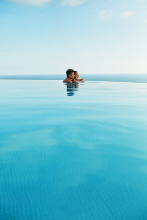 couple relaxing: Couple In Love At Luxury Resort On Romantic Summer Vacation. People Relaxing Together In Edge Swimming Pool Water, Enjoying Beautiful Sea View. Happy Lovers On Honeymoon Travel. Relationship, Romance