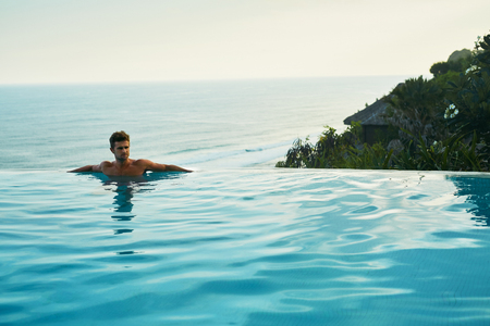 Luxury Resort. Man Entspannung im Infinity-Pool Wasser. Schöne glückliche gesunde männliche Modell, das Sommer genießt Reise Ferien zu Tropical Spa Hotel in Indonesien, Meerblick. Sommerzeit Relax-Konzept