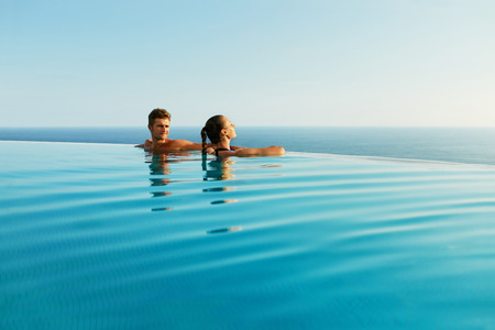 Couple In Love At Luxury Resort On Romantic Summer Vacation. People Relaxing Together In Edge Swimming Pool Water, Enjoying Beautiful Sea View. Happy Lovers On Honeymoon Travel. Relationship, Romance