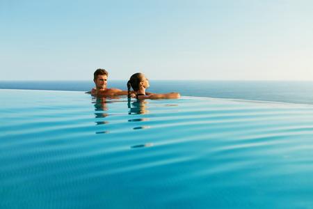 高級リゾート ロマンチックな夏休みに愛のカップル。エッジ プールの水、美しい海の景色を楽しんで、一緒にリラックスの人々。新婚旅行で幸せな