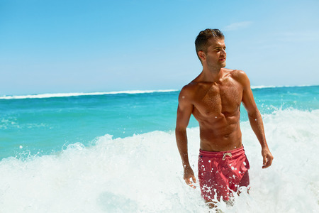 Uomo Sexy Sulla Spiaggia In Estate. Maschio bello con corpo corposo, pelle sana Sun Tan che esce dal mare al lusso Relax Spa Resort. Bel ragazzo felice che si distende, godendo le vacanze di vacanza di viaggio. Estate Archivio Fotografico