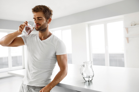 Zbliżenie portret przystojny młody człowiek z Sexy Fit Ciało picia świeżą wodą ze szkła w rano.