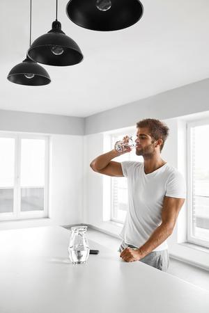 sediento: Agua potable. Apuesto hombre joven con el atractivo del cuerpo en forma de agua potable fresca de vidrio en la mañana. Sed Modelo masculino de la aptitud que disfruta de la bebida refrescante Interior. Concepto de nutrición saludable
