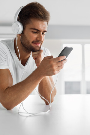 home entertainment: Music Listening. Closeup Portrait Of Handsome Happy Man In Fashion Headphones Using Mobile Phone, Smartphone Indoors. Beautiful Smiling Male Enjoying Music Home. Entertainment, Communication Concept