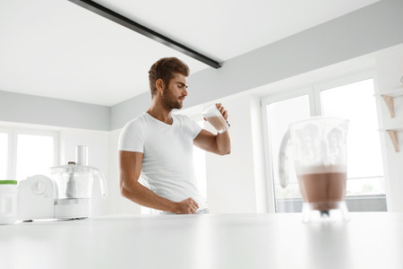 Healthy Eating. Muscular Man With Strong Muscles Drinking Protein Shake In Kitchen. Athletic Beautiful Sexy Fitness Male Model Enjoying Sports Drink Indoors. Bodybuilding Nutrition, Food Supplements