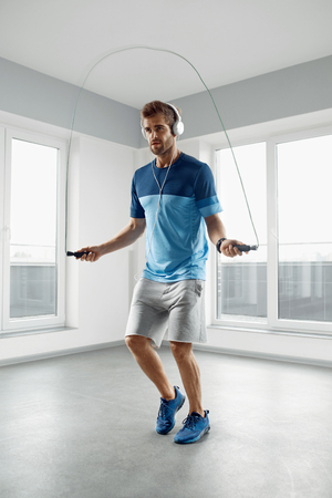 muscular body: Sport And Fitness Workout. Healthy Athletic Man With Muscular Body In Fashion Headphones, Sportswear Skipping With Jump Rope, Exercising Indoor. Handsome Male Doing Jumping Cardio Exercise Training. Stock Photo