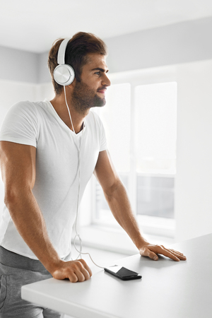 home entertainment: Music Listening. Portrait Of Handsome Muscular Happy Man In Fashion Headphones Using Mobile Phone, Smartphone Indoors. Beautiful Sexy Smiling Male Enjoying Music At Home. Entertainment Concept