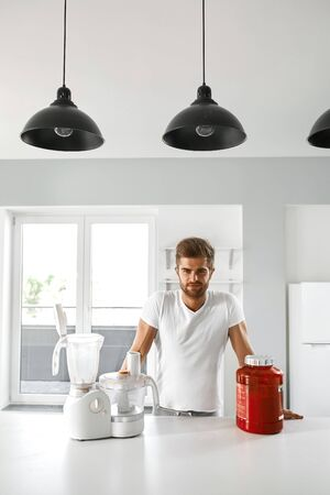 prepare: Sport Nutrition. Healthy Happy Smiling Muscular Man Going To Prepare Protein Shake Drink. Handsome Sexy Fitness Male With Blender And Whey Powder Jar In Kitchen. Bodybuilding Food Supplements Concept