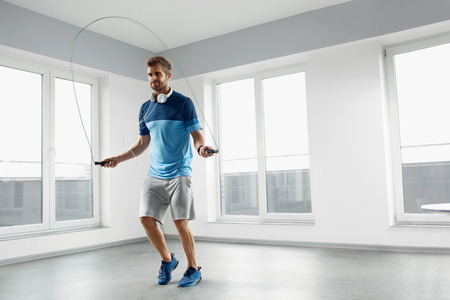 skipping rope: Sport And Fitness Workout. Healthy Athletic Man With Muscular Body In Fashion Headphones, Sportswear Skipping With Jump Rope, Exercising Indoor. Handsome Male Doing Jumping Cardio Exercise Training. Stock Photo