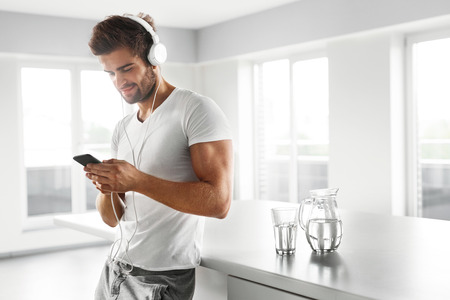 home entertainment: Man Listening To Music In Fashion Headphones Using Mobile Phone, Smartphone Indoors. Portrait Of Handsome Happy Relaxed Smiling Guy  Enjoying Music At Home. Entertainment, Communication Concept