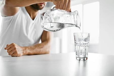 水を飲みます。ハンサムな若い男の台所で朝のグラスに投手から新鮮な純粋な水を注ぐをクローズ アップ。美しいスポーツの男性のモデルは渇いた
