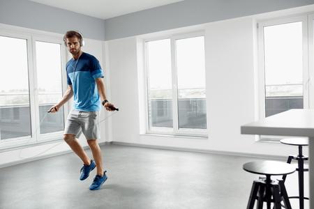 スポーツとフィットネスのワークアウト。健康運動を持つ男ファッション ヘッドフォンで筋肉ボディ屋内運動縄跳びがスキップしたりスポーツウェ 写真素材