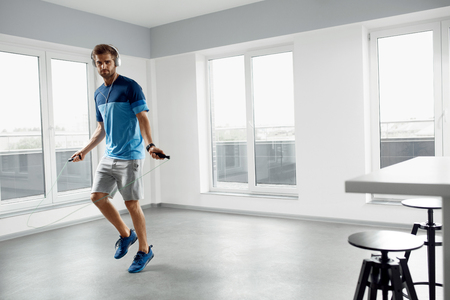 Sport And Fitness Workout. Healthy Athletic Man With Muscular Body In Fashion Headphones, Sportswear Skipping With Jump Rope, Exercising Indoor. Handsome Male Doing Jumping Cardio Exercise Training. Zdjęcie Seryjne