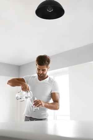 acqua bicchiere: Bere acqua. Bello Giovane Sorridente dolce acqua pura Versando Da Brocca In Un Bicchiere mattino in cucina. Bella Athletic Male Model sensazione di sete. Sana alimentazione e l'idratazione Concetto