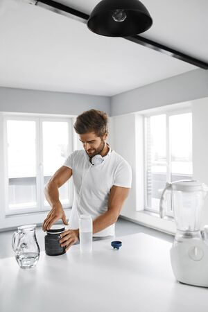 amino: Sport Nutrition. Healthy Handsome Man With Fit Body Preparing Energy ???? Shake In Bottle In Kitchen. Sexy Muscular Male Making Drink Before Fitness Workout. Sports Bodybuilding Amino Acid Supplements