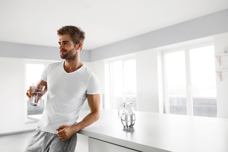 Drinking Water. Closeup Portrait Of Handsome Young Man With Sexy Fit Body Drinking Fresh Water From Glass In Morning. Thirsty Fitness Male Model Enjoying Refreshing Drink Indoors. Healthy Nutrition Banco de Imagens