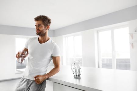 Wasser trinken. Nahaufnahme Portrait der schönen jungen Mann mit sexy Fit Körper Süßwasser aus Glas in der Morgen-Trinken. Thirsty Fitness Male Model genießen Refreshing Innenaufnahme Getränk. Gesunde Ernährung