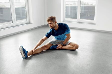 athletic body: Stretch Body Exercise. Handsome Man Stretching Before Workout. Healthy Muscular Athletic Active Fitness Male Model In Fashion Sportswear Doing Stretches, Warming Up, Exercising Indoors. Sports Concept Stock Photo