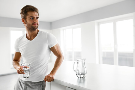 Healthy Nutrition. Handsome Young Man With Sexy Fit Body Holding A Glass Of Fresh Water In Kitchen. Athletic Smiling Fitness Male Drinking Water In Morning. Hydration, Health And Drink Concepts.