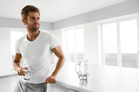 Nutrición saludable. Apuesto hombre joven con el cuerpo en forma atractiva que sostiene un vidrio de agua dulce en la cocina. Atlético sonriente masculino de la aptitud Agua Potable En la mañana. Hidratación, la salud y los conceptos de bebidas. Foto de archivo