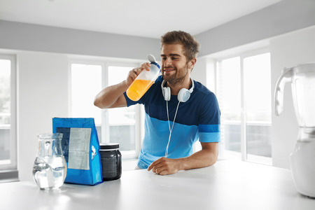 Drinking Sports Drink. Healthy Handsome Happy Man With Muscular Body In Sportswear Drinking Beverage ???? Before Fitness Exercising Indoors. Bodybuilding Nutrition, Amino Acid Supplements On Table 스톡 콘텐츠