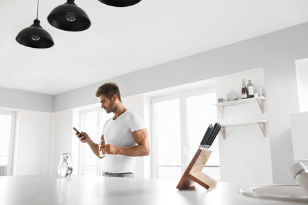 hydration: Healthy Nutrition. Handsome Young Man With Sexy Fit Body Holding A Glass Of Fresh Water While Using Mobile Phone In Kitchen. Smiling Male Drinking Water In Morning. Hydration, Health And Drink Concept