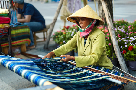 VIETNAM, HO CHI MINH - FEBRUARY 6, 2016: Portrait Of Vietnamese Woman In Traditional Conical Hat, Non La Weaving Yarn On Street. Female Textile Weaver Preparing Warp On Hand Backstrap Loom Outdoors